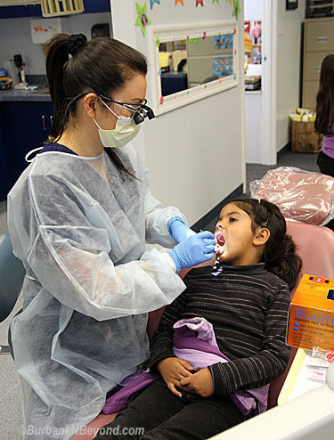 Yuka Aoki, a Dental Hygienist in training, spends time helping  Emily Quintana      (Photo By Ross A. Benson)