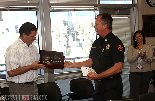 Retired Burbank Arson Investagator John Nare accepts his retirement shadow box of his patches and badge from Chief Ray Krakowski.  (Photo by Ross A. Benson)