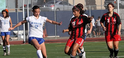 Burbank High's Alessia Dal-Monte takes a kick as Burroughs Alexis Mendias works the field. (Photo by Ross A. Benson)