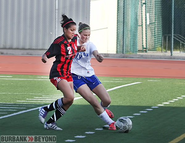 Burroughs High's Lilith Paparo-Prieto tries to take the ball from Burbank High's Natalie Muller. ( Photo by Ross A. Benson)