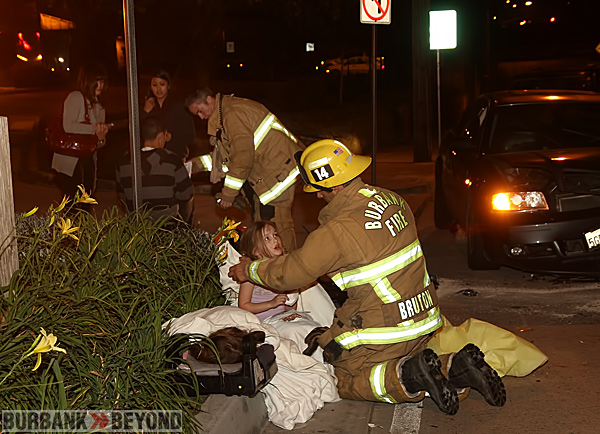 Burbank Firefighter Clint Burton comforts a child following this accident on Victory Place Wednesday evening.  (Photo by Ross A. Benson)