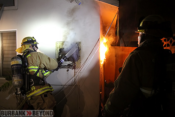 Burbank Firefighters work to extingsh a fire within the wall of a house on Niagara St. (Photo By Ross A. Benson)