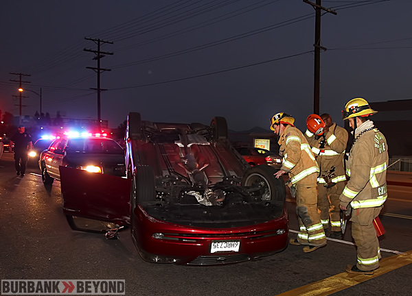 Burbank Firefighter secure this overturned auto that struck a parked car and overturned, causing NO injuries. (Photo by Ross A. Benson)