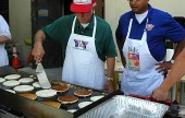 Burbank YMCA Service Club members Art Wetton, left, and Arnie Lee parpare pancakes for the fund-raising breakfast on May 12. (Photo by Joyce Rudolph)