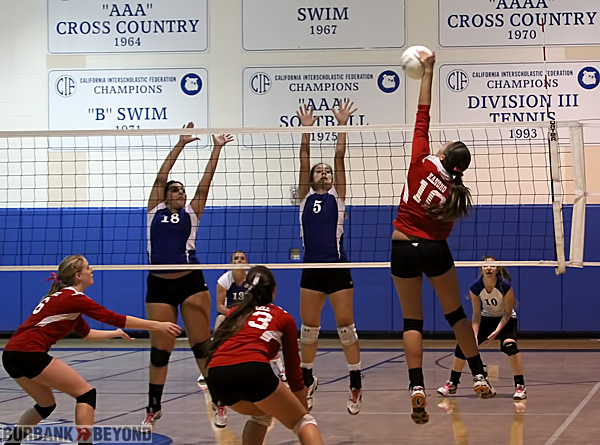 Burroughs Autim Kanoho goes for a hit while Burbank's Stephanie Eskander, #18, and Denise Daniel, #5, go for the block (Photo by Ross A. Benson)