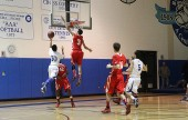 Burroughs' Lawrence White, #3, goes high above the basket to block the shot of Burbank's Peter Wongsasitorn (Photo by Ross A. Benson)