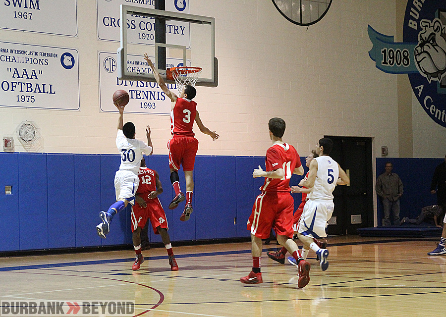 Burroughs Lawrence White, #3, goes high above the basket to block the shot of Burbank's Peter Wongsasitorn (Photo by Ross A. Benson)