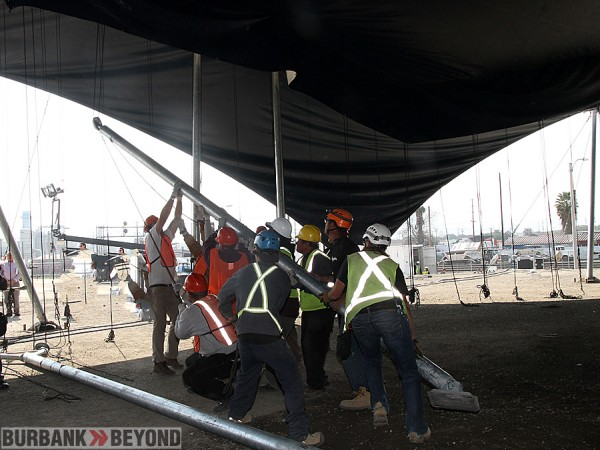 Labors erect one of the side poles that will hold the side canvas in place. (Photo by Ross A. Benson)