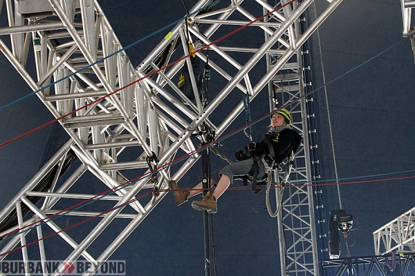 Electrician Marie Elyse Lamy hangs from truss, as she secures electrical equipment, the total weight of equipment that will be hung on the technical grid is 80 tons of gear. (Photo by Ross A. Benson)
