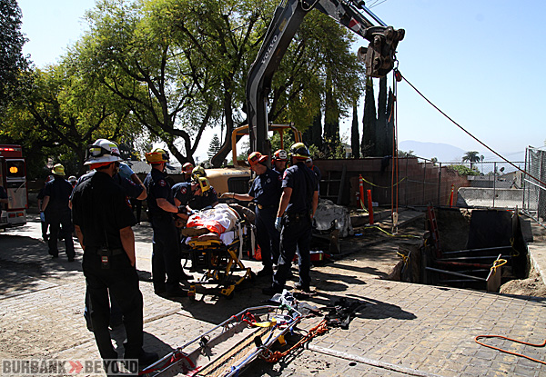 Burbank Fire Fighters & Paramedics package up a worker who fell over 20 feet into a trench on Sunset Cyn. & Magnolia Blvd. Friday afternoon. (Photo by Ross A. Benson)