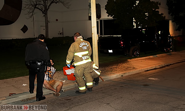 Burbank Police & Firefighters talk to the driver of the pictured truck after he crashed it into a water valve. (Photo y Ross A. Benson)