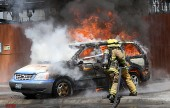Recruit Firefighters extinguish a set auto fire during graduation exercises Friday at The Burbank Training Center. (Photo by Ross A. Benson)