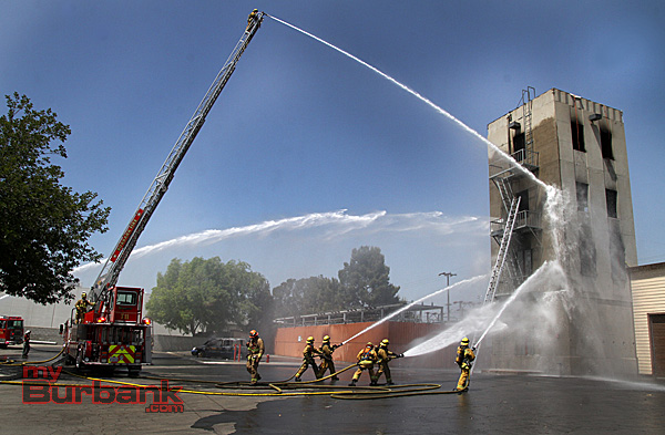 Flowing water from Truck 11 and Engine 11 while fire recruits man handlines during graduation exercises Friday. (Photo by Ross A. Benson)