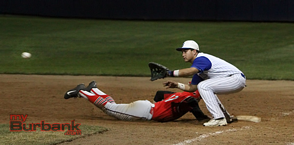 A Burroughs player dives back safely as first baseman Harrison Hernandez prepares to catch the ball (Photo by Ross A. Benson)