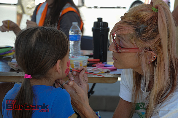 Jacqueline Licciardi, who also works as a fitness instructor and personal trainer, paints a bright flower on 8 year-old Kiana Bohrer (Photo By Craig Sherwood)