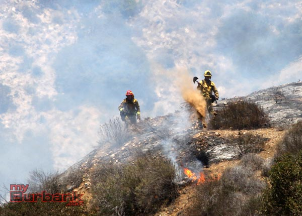 A Burbank Firefighter uses a shovel of dirt to douse a a small flareup in the hills above DeBell Golf Course Monday afternoon. (Photo by Ross A. Benson)