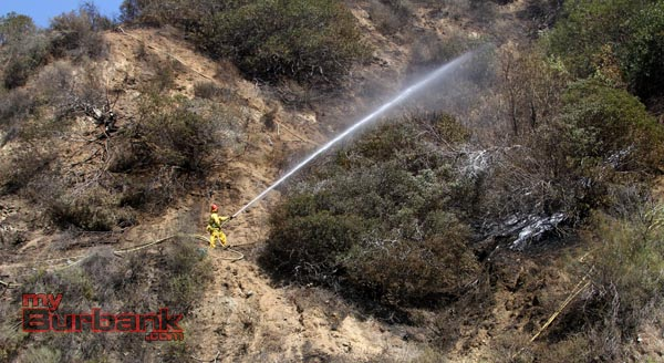 Burbank Firefighter sprays water on the hillside along the 16th holes of DeBell where a small brush fire consumed 1 acre Monday afternoon. (Photo by Ross A. Benson)