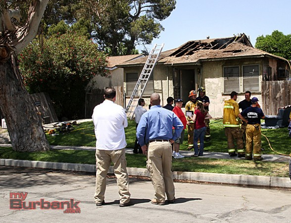 Neighbors look on to the damage that was caused, to the roof after fire ripped through the residents. (Photo by Ross A. Benson)