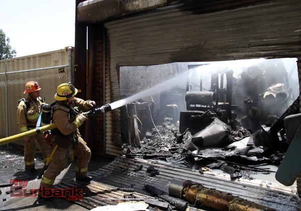 Glendale Firefighters hit some hots spots inside the backdoor of Beauty Kiss Carpets. (Photo by Ross A. Benson)