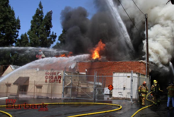 Flames shoot thru the roof of Beauty Kiss Carpets.(Photo by Ross A. Benson)