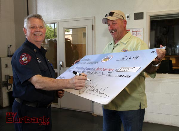 Burbank Firefighters Local 778 Director Peter Henderson sign a BIG check in the amount of $3500.00, as Jeff Howe from Quest assists.(Photo by Ross A. Benson)