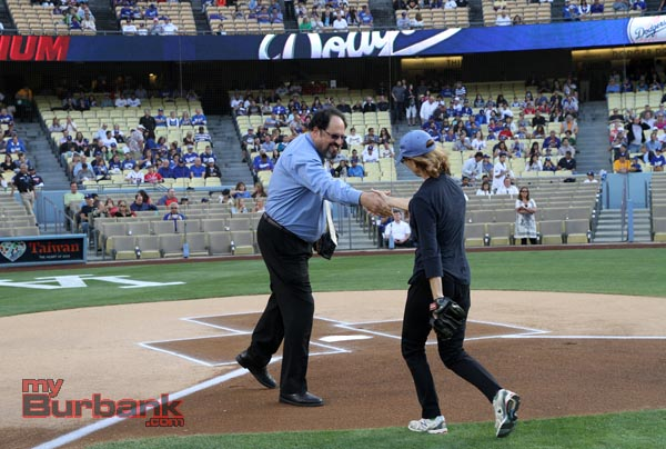 Vice Mayor David Gordon congratulates Mayor Emily Gabal Luddy at home plate after a successful pitch to home plate. (Photo by Ross A. Benson)
