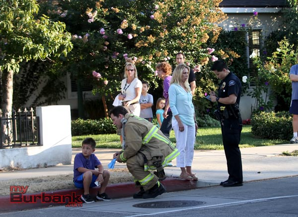 Burbank Firefighter John Freeborn checks out one of the passengers that was involved in this accident,and making sure he's OK, while a Burbank Police officer gathers information(Photo by Ross A. Benson)