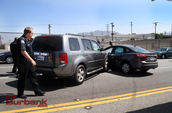 Lt. Matthew Ferguson checks the damage of these 2 car that collided on the Burbank Overpass. (Photo by Ross A. Benson)