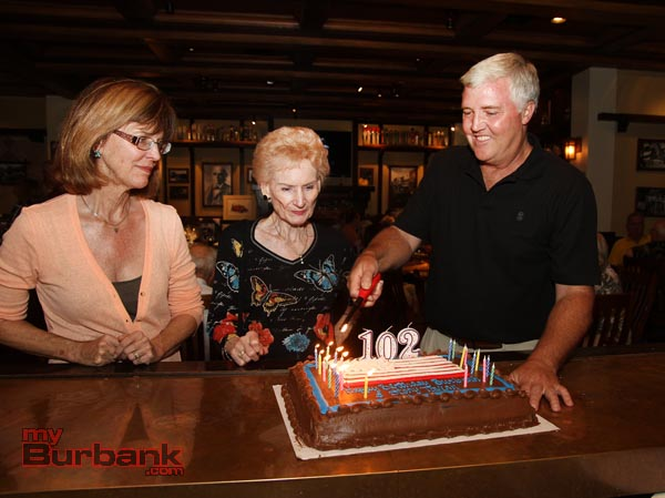 Burbank Mayor Emily Gabal-Luddy, Mary Jane Strickland with Ted Slaught lighting the Birthday candles on a huge cake.(Photo by Ross A. Benson)
