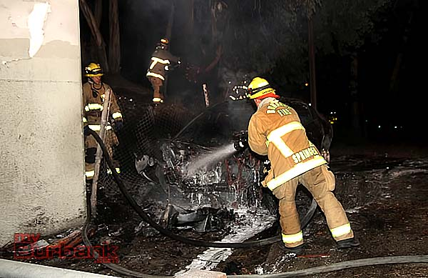 Burbank Firefighter Kyle Springer puts out flames coming from a Nissan after it struck a guardrail and burst into flames. (Photo copyrighted By Ross A. Benson)