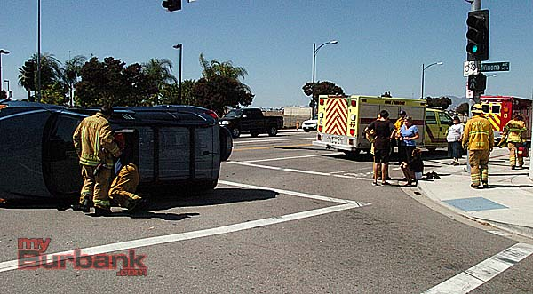 Firefighters check out a car after assisting victims out of the vehicle (Photo By Nick Colbert)