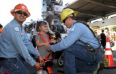 Chris Vilchis makes sure Katelyann is secured in a safety harness. (Photo by Ross A. Benson)