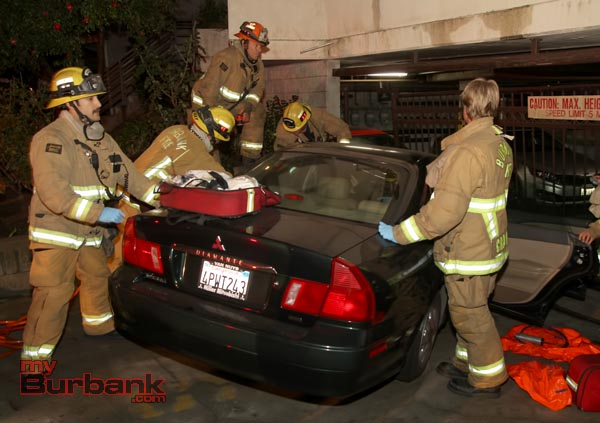 Burbank Firefighters work to free the drivers foot from her car-door after her car struck a wall and the garage gate as she was trying to exit her car at 1905 Scott Road. (Photo by Ross A. Benson)