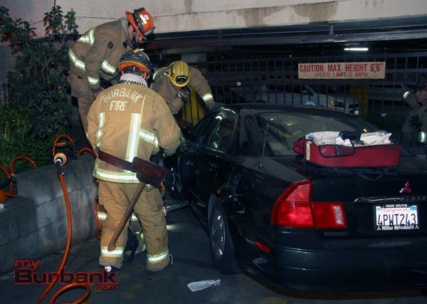 Burbank Firefighters use the 'Jaws of Life' to free the drivers foot from her car-door after her car struck a wall and the garage gate as she was trying to exit her car at 1905 Scott Road. (Photo by Ross A. Benson)