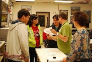 Tuck Tucker works with BHS students, prepping their storyboard presentation. (Photo By Lisa Paredes)