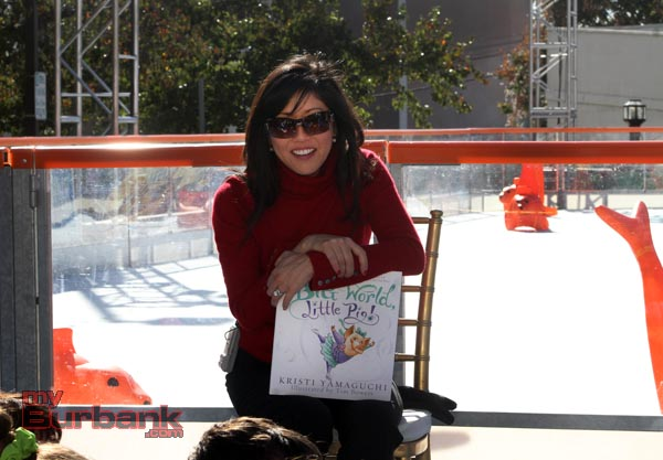 """Olympian Kristi Yamaguchi reads from her book """"It's a big world, little pig!"""" during her visit at  The Rink on Wednesday. (Photo by Ross A. Benson)"""