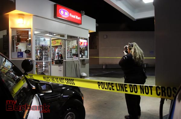 Burbank Police Forensic Specialist Victoria Payson records photographic evidence of robbery location at the Chevron Olive & Buena Vista. ( Photo by Ross A. Benson)