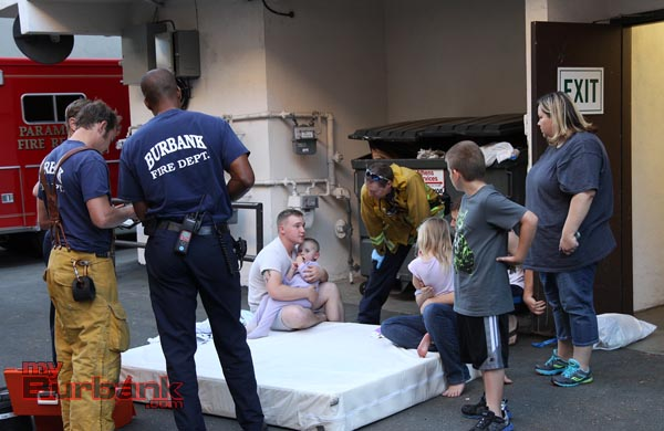 Burbank Fire Fighters and Paramedics speak to the father holding his 3 year old after the baby fell from a second story window. ( Photo by Ross A. Benson)