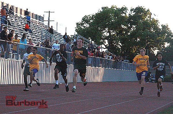 Julian Read of Luther Burbank (center) sprints his way into the record books in the 100 meter dash (Photo by Dick Dornan)