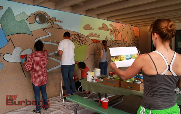 Katie Heckey checks the progress of the mural painting. (Photo by Ross A. Benson)