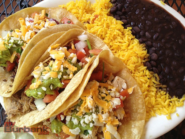 A trio of tacos - pork, chicken and beef - are propped up by Cuban rice and beans.  (Photo By Lisa Paredes)