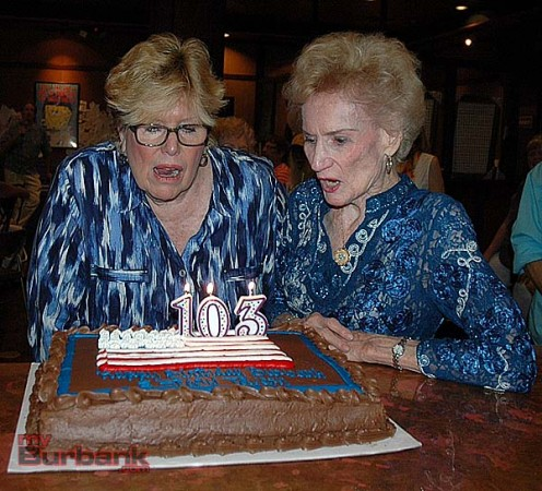 Burbank Historical Society President Sue Baldaseroni, left, blows out the candles with museum founder Mary Jane Strickland. The anniversary party honored the 103rd anniversary of the incorporation of the city of Burbank -- July 11, 1911. (Photo by Joyce Rudolph)