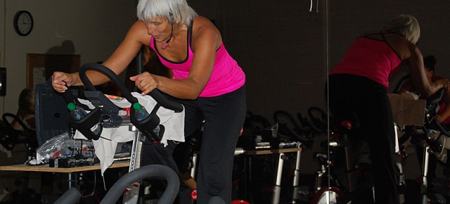 JoDee Geryak works through resistance on the spin bike at the YMCA. (Photo By Lisa Paredes)