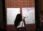 A friend writes her condolences on a poster dedicated to former Burroughs football player, Jake Gnasso (Photo by Ross A. Benson)