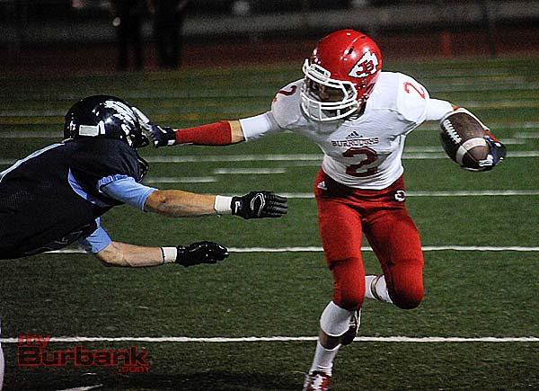 Burroughs' Erick Hernandez stiff arms a Falcon defender (Photo by Craig Sherwood)