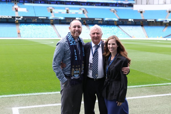 Ian and Shannon MacLeod, with Manchester City Football Club Ambassador Mike Summerbee (center), on the pitch. (Photo Courtesy of Manchester City Football Club)