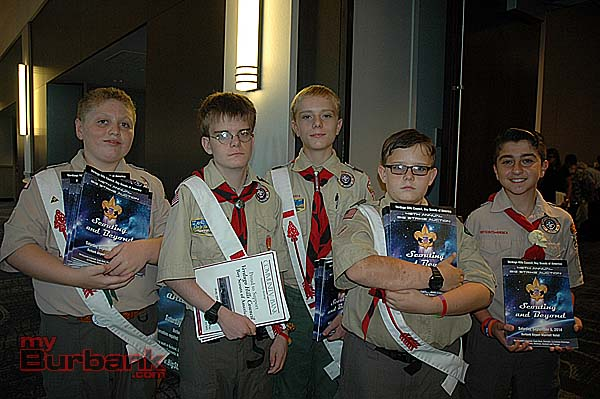 Boy Scouts distributing programs are, from left, Liam KcKenna of Troop 219; brothers Sean, Daniel and Peter Rawlins, of Troop 139; and Sako Kitsinian of Troop 201. (Photo by Joyce Rudolph)