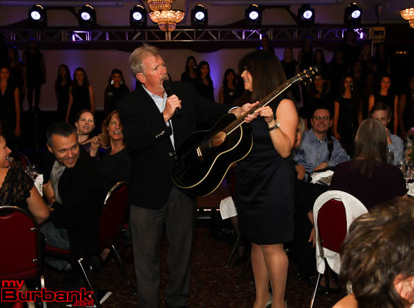 Auctioneer Bruce Osgood with VMA Ellie Stockwell show a Neil Diamond signed guitar that went for $1300.00.  (Photo by Ross A. Benson)