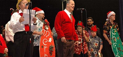 """Mark Nakamura, left, and Ernie Pistacchio, at the microphones, lead clients in """"O Holy Night"""" during the Holiday Program presented by BCR """"a place to grow"""". (Photo by Joyce Rudolph)"""