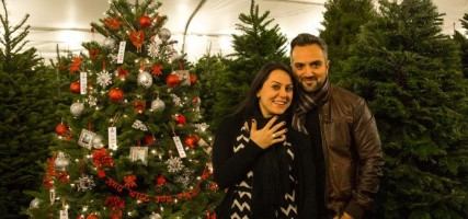Angineh Almasi and Patrick Keshishzadeh stand beside the decorated Christmas tree at the Burbank Community YMCA Christmas Tree Lot where she accepted his wedding proposal on Friday. (Photo courtesy Arnis Zargarian)